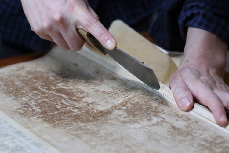 丸包丁と呼ばれる大きな刀で、下軸に巻いた紙だけを丁寧に切っていきます。