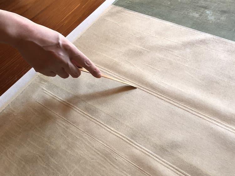 紙と紙との重なりにできる段差には、ヘラをぴっちりと当てて隙間をなくし、中の浮きをなくしていきます。