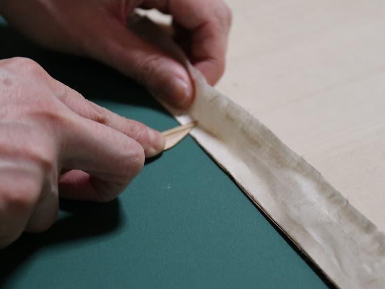 はみ出ている部分を耳のほんの少し内側に折り曲げて、竹ヘラで撫で込んでいきます。