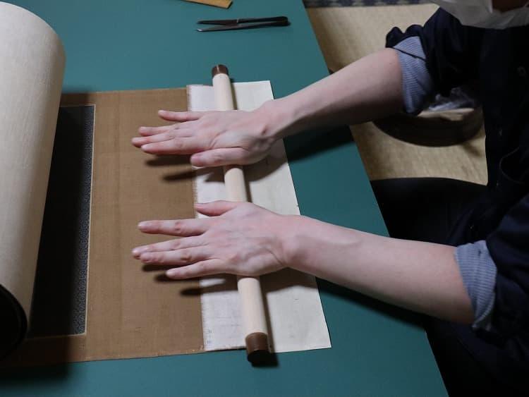 軸袋部分を開いてその間に軸木を据えて、糊を付けて巻きます。